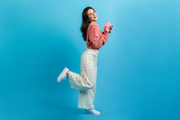 青い壁にピンクのカメラでポーズをとる流行の明るい服装の女の子。魅力的な笑顔の女性がコケティッシュに脚を上げた。