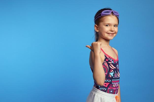 Девушка в модном купальнике и плавательных очках указывает в сторону, улыбаясь