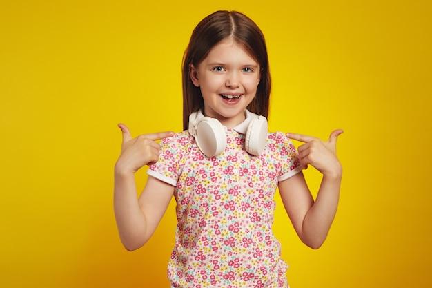 Девушка в футболке и наушниках, указывая на себя с веселым выражением лица