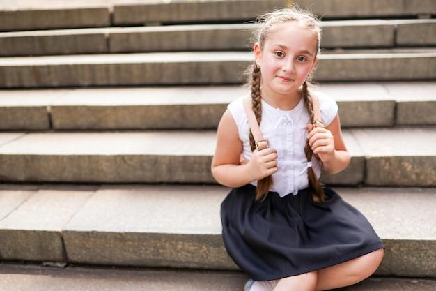 Девушка в форме и белой блузке с рюкзаком сидит на ступеньках возле школы.