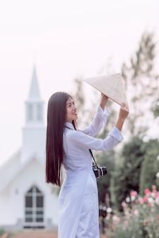 Девушка в национальном костюме вьетнама стоя со шляпой, чтобы счастливо улыбаться