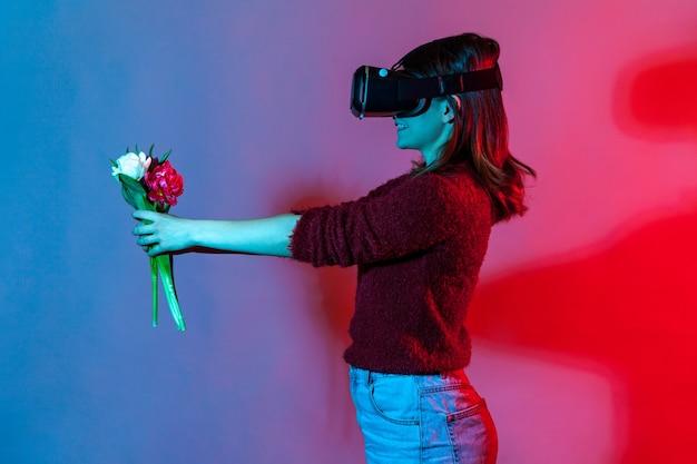 Девушка в очках виртуальной реальности держит букет цветов, дарит тюльпаны виртуальному другу и улыбается