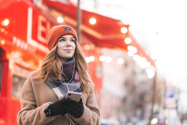 따뜻한 옷을 입은 소녀는 그녀의 손에 스마트 폰을 들고 거리에 서서 헤드폰으로 음악을 듣는다.