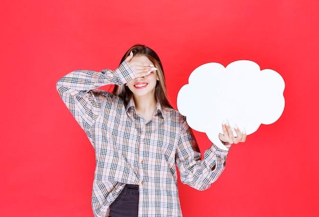 Девушка в теплом свитере держит доску с идеей в форме облака и чувствует себя усталой из-за этого занятия