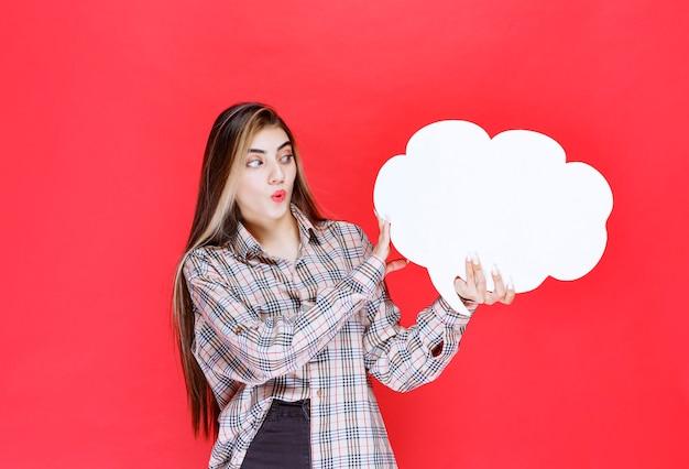 雲の形のアイデアボードを保持し、驚いたように見える暖かいセーターの女の子