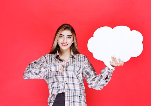 Девушка в теплом свитере держит доску с идеями в форме облака и представляет задачу