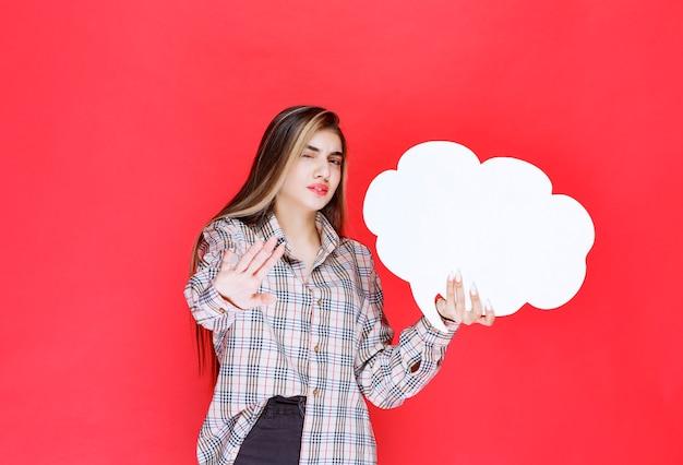 Девушка в теплом свитере держит доску с идеями в форме облака и отказывается играть в нее