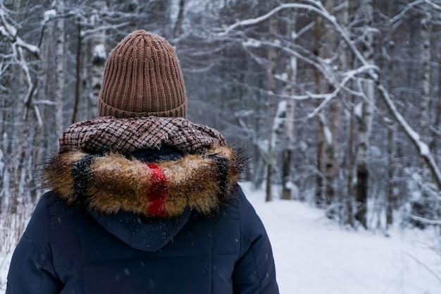 눈 덮인 공원에서 시청자에게 등을 대고 따뜻한 겨울 옷을 입은 소녀