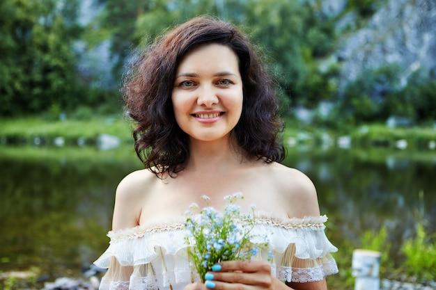 ウェディングドレスの女の子は、野花と笑顔の花束、クローズアップを手に持っています。