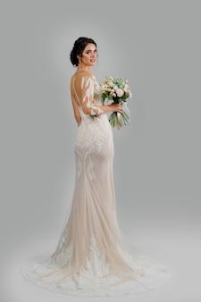 Девушка в свадебном платье на белой глухой стене. невеста в белом свадебном платье с букетом в студии.