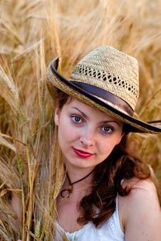 白いドレスとステットソン帽子の麦畑の女の子。セレクティブフォーカス。