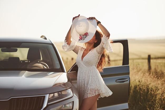 현대 럭셔리 자동차 야외 근처 포즈 흰 옷을 입고 소녀