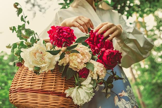 정원 여자 꽃집 손에 모란 꽃 바구니와 함께 흰색 옷을 입고 소녀를 닫습니다