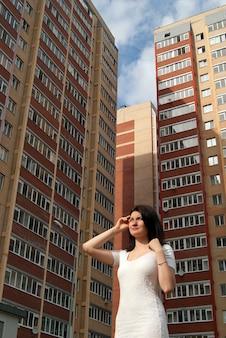 Девушка в белом платье на фоне многоэтажных жилых домов