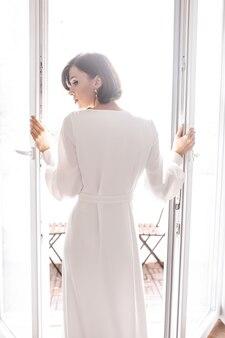 Девушка в белом платье открывает дверь на балкон