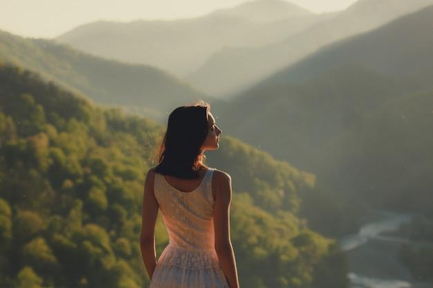 川のある緑の谷で夕日に風景を望むコーカサス山の頂上に立っている白いドレスの女の子。女性旅行の性質の概念