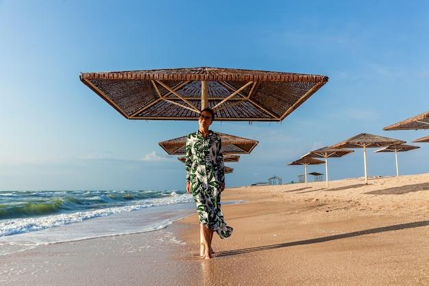Девушка в белом платье с зелеными листьями позирует на пляже возле зонтика от солнца. девушка в платье позирует на пляже