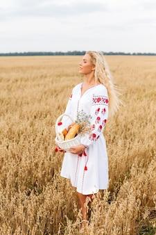 Девушка в белом вышитом платье держит корзину в поле