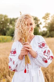 Девушка в белом вышитом платье держит букет колосков в поле