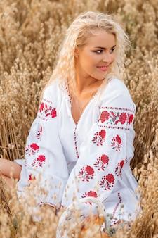 Девушка в белом вышитом платье сидит в поле
