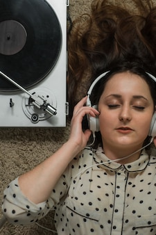 Девушка в белых наушниках на полу слушает проигрыватель.