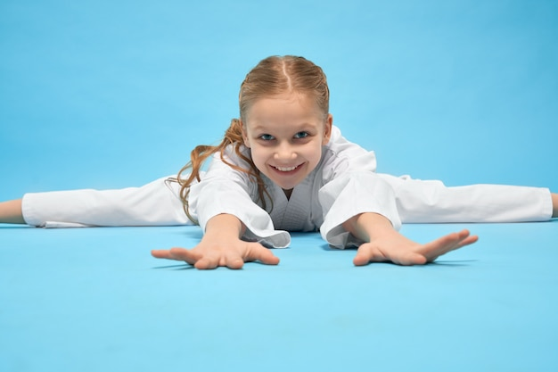 Девушка в белом кимоно, делая шпагат, лежа на синем фоне.