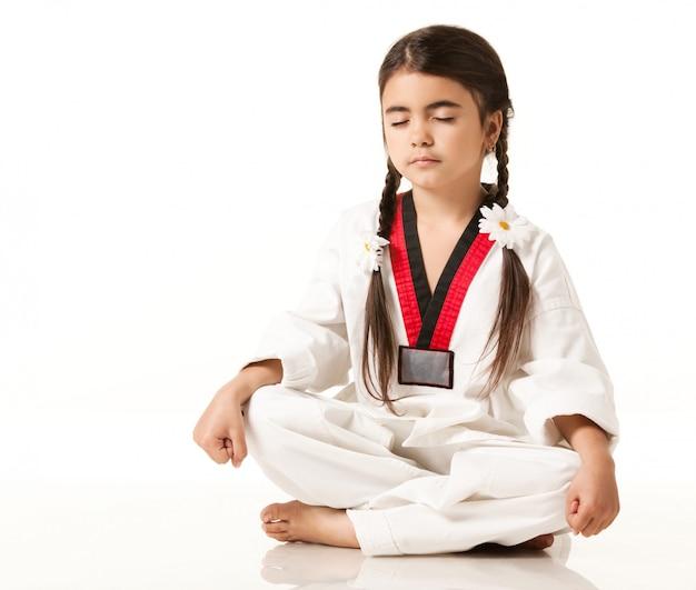 Девушка в белом кимоно сидит в позе йоги