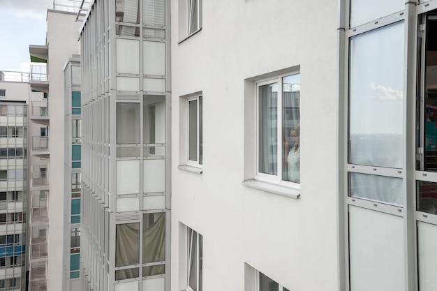 Девушка в белой мужской рубашке смотрит в окно и эмоциональна. портрет красивой женщины. домашний уют и ожидание. славянская самка по утрам. эмоции и расслабление. концепция проживания в семье