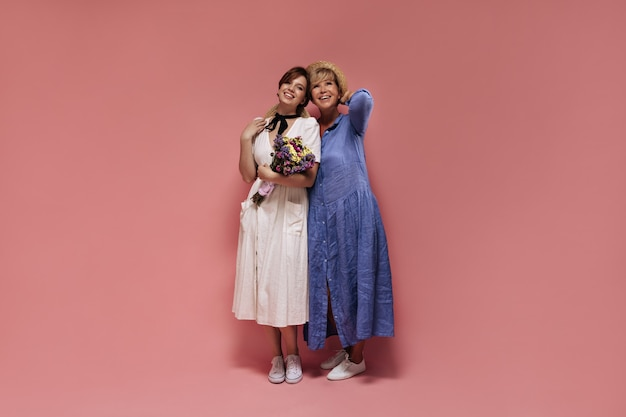 白いミディドレスと野生の花を保持し、ピンクの背景に青い服を着た金髪の女性と笑顔でポーズをとる麦わら帽子の女の子。