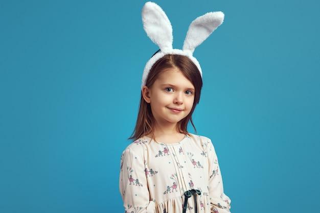Девушка в белой рубашке и кроличьих ушах очаровательно позирует на синей стене