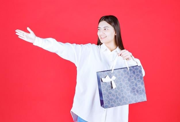 파란색 쇼핑백을 들고 선물할 사람을 초대하는 흰색 셔츠를 입은 소녀
