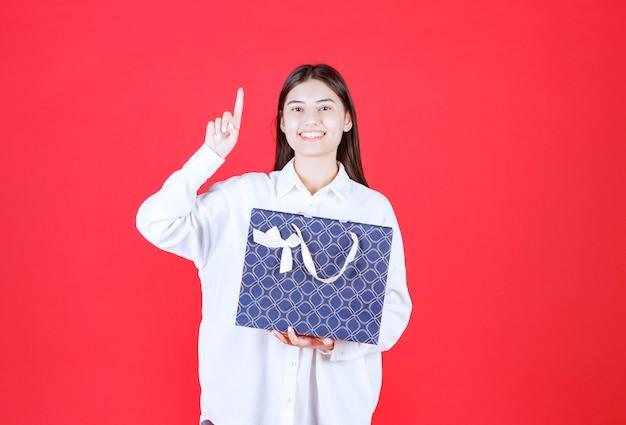 Девушка в белой рубашке держит синюю сумку для покупок и выглядит смущенной и задумчивой