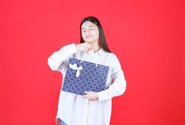 Девушка в белой рубашке держит синюю сумку для покупок и выглядит сонной и уставшей
