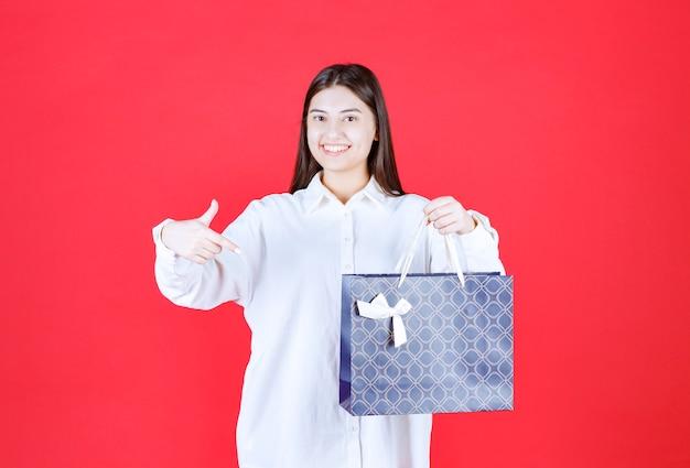 Девушка в белой рубашке держит синюю сумку для покупок