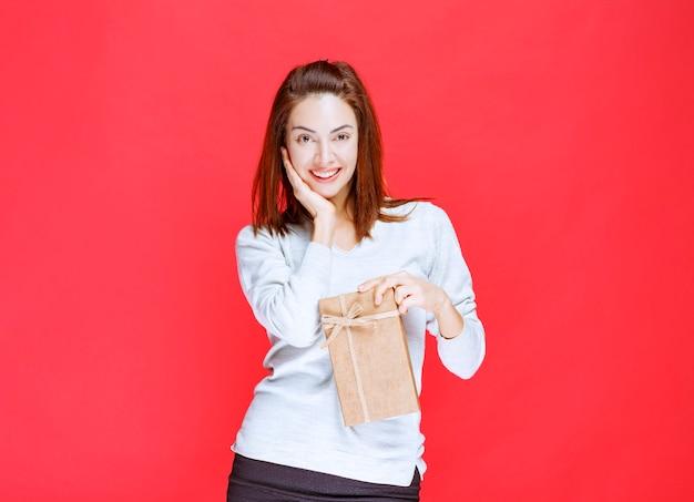 ギフトボックスを持って驚いたように見える白いシャツの女の子。