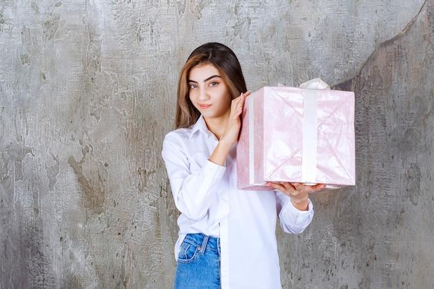 白いリボンで包まれたピンクのギフトボックスを持っている白いシャツの女の子は、混乱して躊躇しているように見えます。