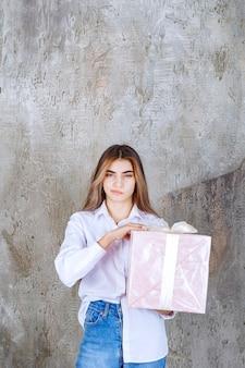 Девушка в белой рубашке держит розовую подарочную коробку, обернутую белой лентой, и выглядит смущенной и нерешительной.