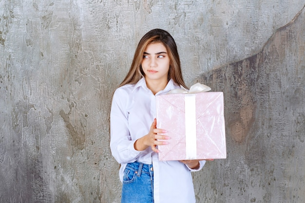 白いリボンで包まれたピンクのギフトボックスを保持し、混乱して躊躇しているように見える白いシャツの女の子