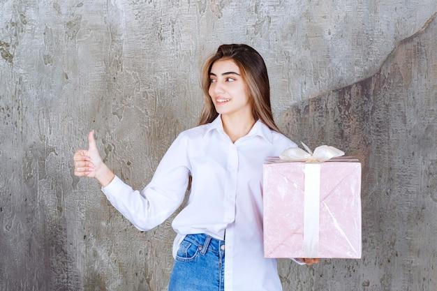 Девушка в белой рубашке держит розовую подарочную коробку, обернутую белой лентой и показывает знак рукой