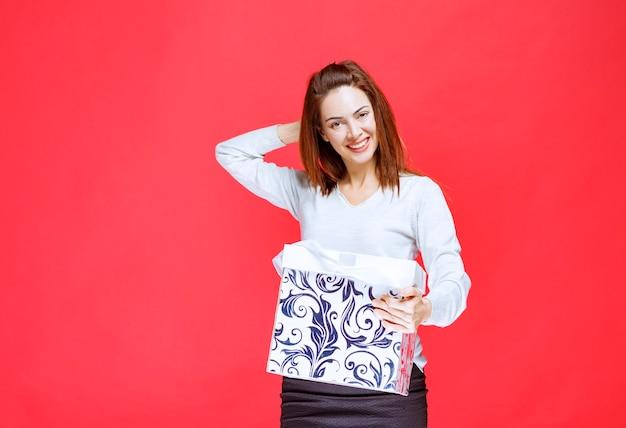 Девушка в белой рубашке держит подарочную коробку с принтом и выглядит растерянной и задумчивой