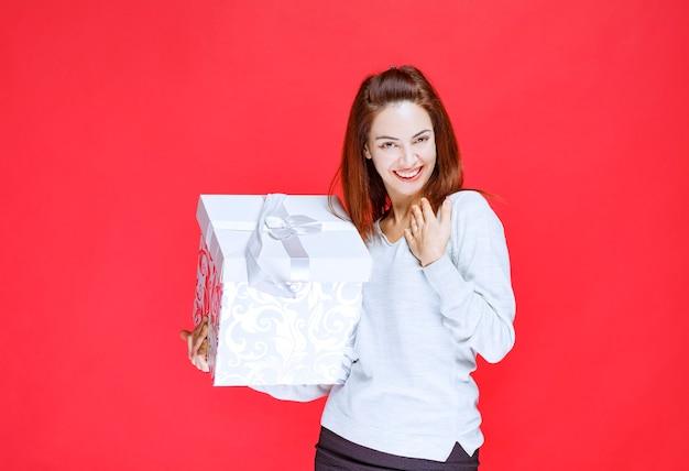 Девушка в белой рубашке держит подарочную коробку с принтом