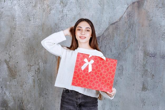 赤い買い物袋を持っている白いシャツを着た女の子は、混乱して思慮深く見えます。