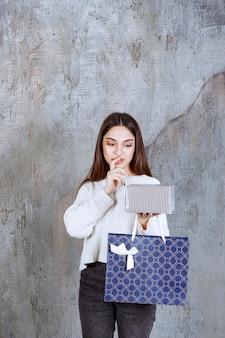 Девушка в белой рубашке держит серебряную подарочную коробку и синюю сумку для покупок и выглядит смущенной и задумчивой, делая выбор.