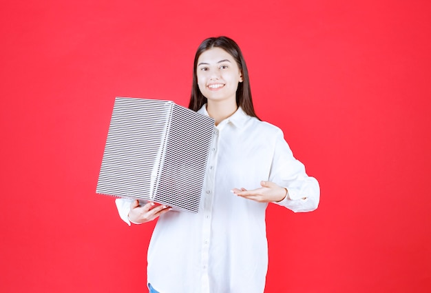 Девушка в белой рубашке держит серебряную подарочную коробку