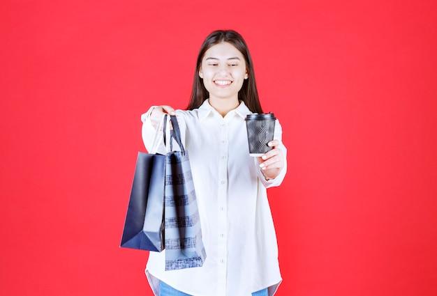 Девушка в белой рубашке держит несколько сумок и делится черной чашкой кофе на вынос