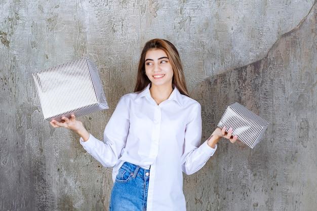 Девушка в белой рубашке держит серебряные подарочные коробки