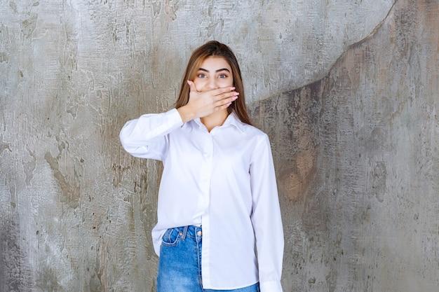 コンクリートの壁に立って、怖いと恐怖を感じている白いシャツの女の子