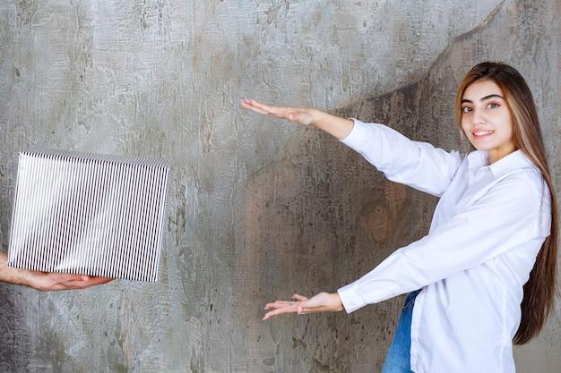 コンクリートの壁に立っている白いシャツを着た女の子は、銀のギフトボックスとそれを取るために憧れの手を提供されています。