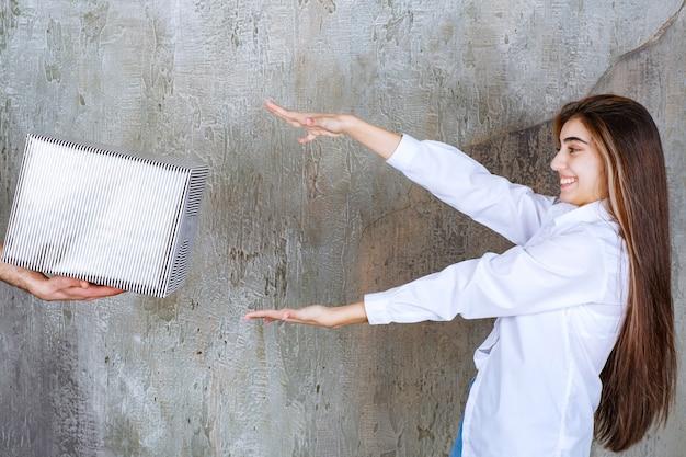 コンクリートの壁に立っている白いシャツの女の子は、銀のギフトボックスとそれを取るために憧れの手を提供されています