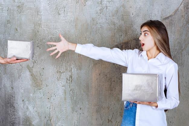 Девушке в белой рубашке, стоящей на бетонной стене, предлагают серебряную подарочную коробку и с нетерпением ждут руки, чтобы взять ее
